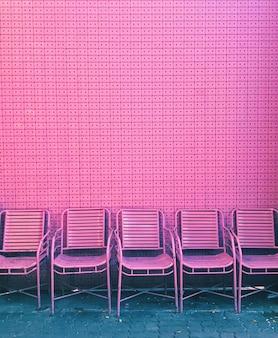 Розовые стулья перед розовой пастельной стеной сделаны из переработанных кассетных лент.