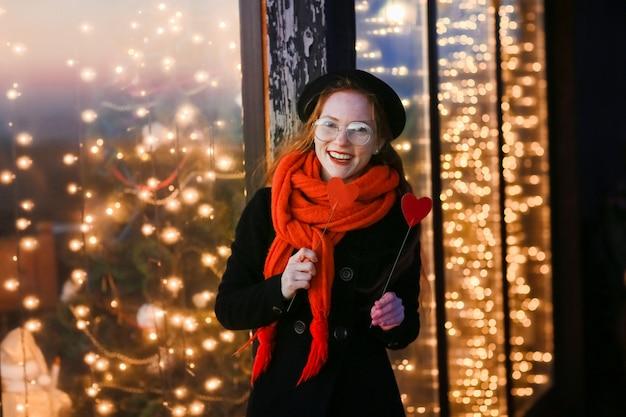 Рыжеволосая девушка на фоне ярких новогодних витрин развлекается и позирует с картонными сердечками в руках