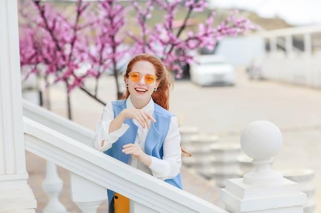 Студентка с хорошим настроением идет к зданию с каменными ступенями