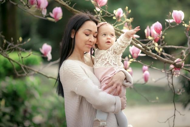 若い母親と秋の公園で小さな娘がマグノリアの葉で遊ぶ。秋の森公園で家族と幸せな週末。公園の人々。笑顔の女性と屋外で赤ちゃん。秋。晴れた日