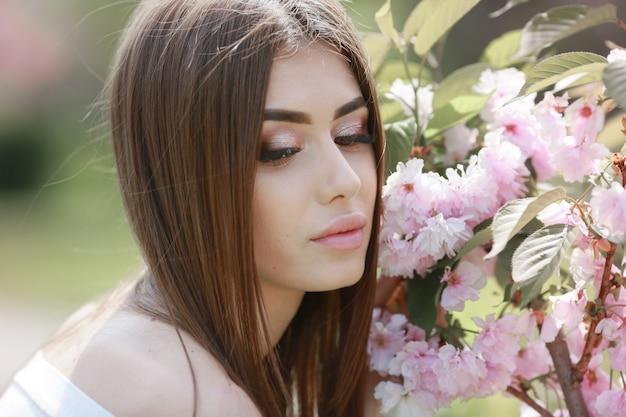 Портрет красивой молодой женщины модели возле розовых веток с цветами сакуры