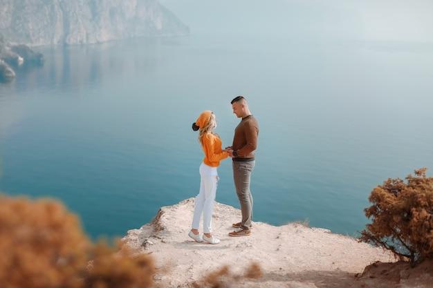 若い男性と女性は、海湾のパノラマの景色を望む山の上に立っています