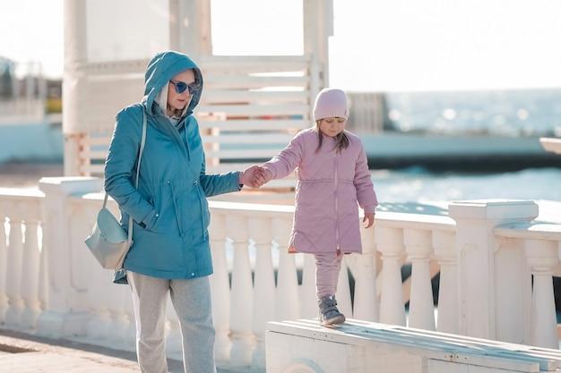 若い母親と小さな娘の散歩
