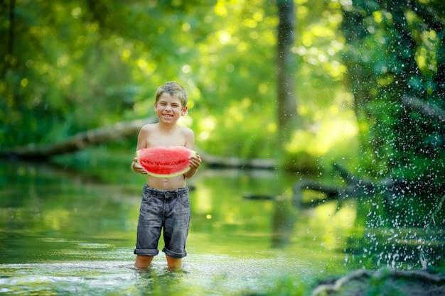 森の川で膝の深いところに立っているショートパンツとシャツのない男の子、赤いジューシーなスイカのスライスを食べる