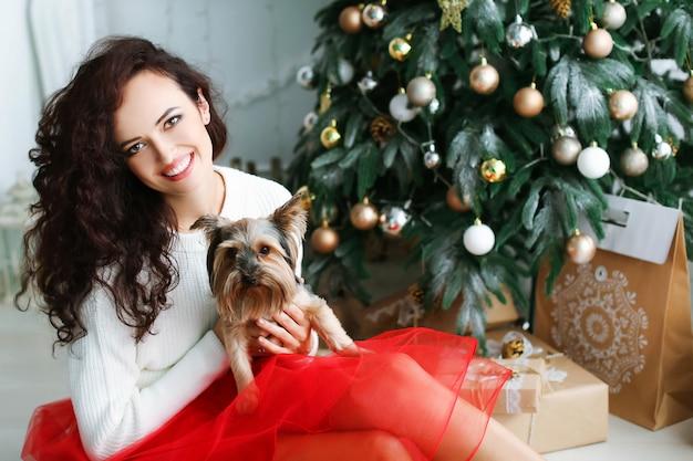 Модель женщины в красном платье в фотостудии с новогодним подарком в руках.