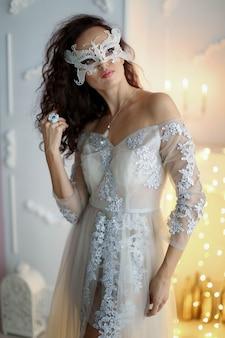 Новогоднее фото модельной девушки в белом платье на фоне желтой яркой новогодней елки.