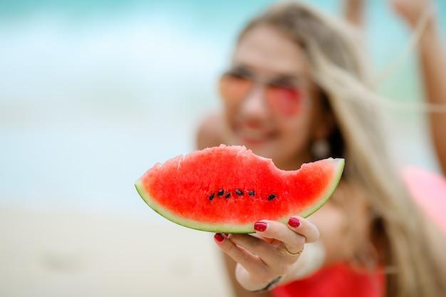 ビーチで女性が海の海岸でベジタリアン料理を食べる