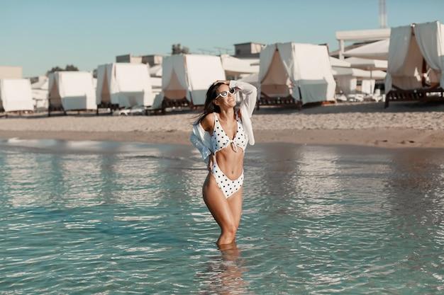 海の端でリラックスしたファッションビキニでセクシーなフィット体を持つ美しい女性