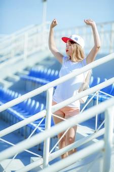 裸足で頭に帽子をかぶったショートパンツの夏のスポーツ表彰台に立つ女性