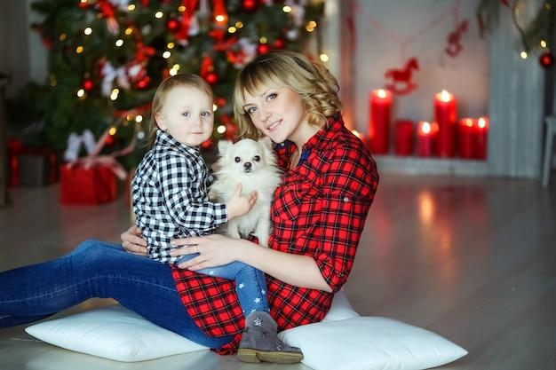 Семья из двух человек мама и в новогоднюю ночь возле украшенной елки сидит на полу с маленьким домашним животным.
