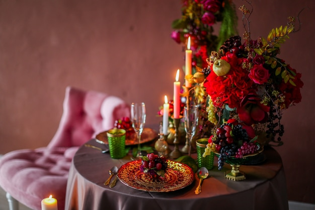 Стол украшен искусственными фруктами и свечами