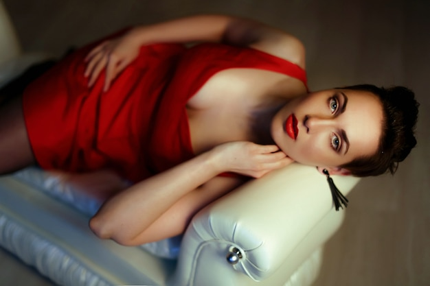 Красивая женщина полного телосложения лежит на белом диване