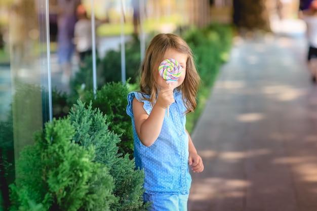 お菓子を手に公園で散歩する子供
