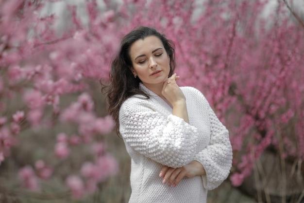 Красивая взрослая женщина с открытыми плечами в свитере на фоне цветущего персикового сада