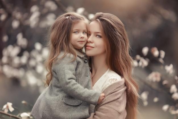 開花白い木を背景に赤ちゃんを持つ母親の肖像画