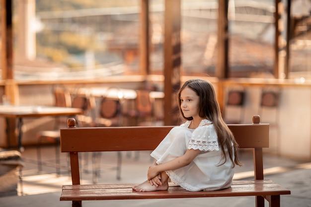 Ребенок с босыми ногами сидит на деревянной скамейке.