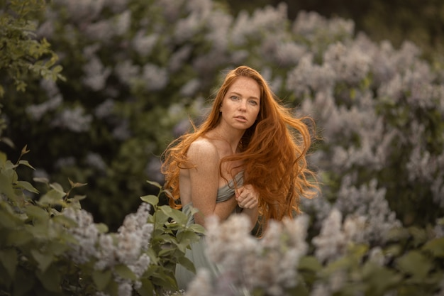 ライラック色の花と茂みの背景に長い赤い髪を持つ女性