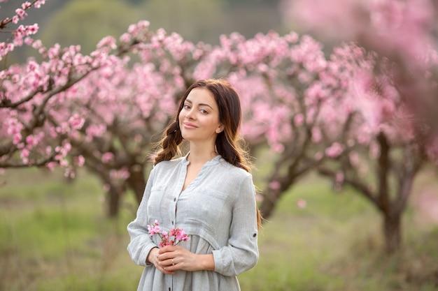 Красивая молодая женщина возле цветущего весеннего дерева