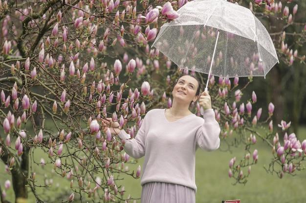Фасонируйте портрет красивой молодой женщины в лесе осени. женщина зонтика