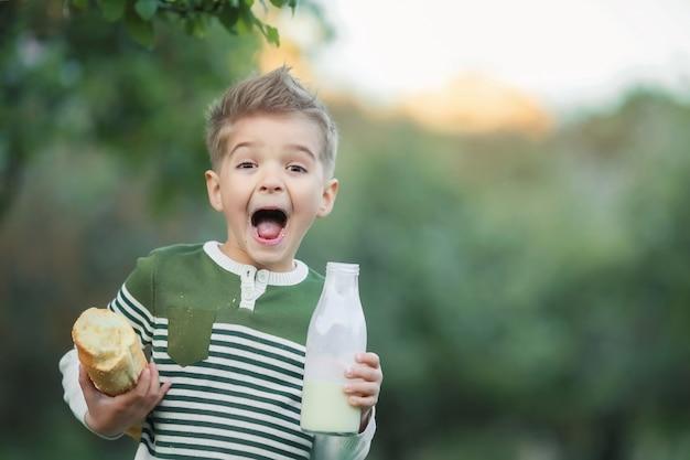 女の子と男の子が牛乳を飲むし、夕暮れ時の村の干し草の山でパンを食べる