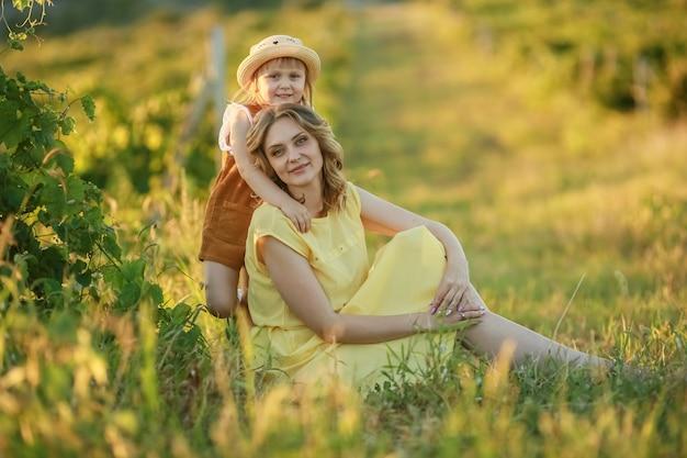 Моя мама сидит в желтом платье на зеленой траве в естественном поле, а моя дочь обнимает ее сзади