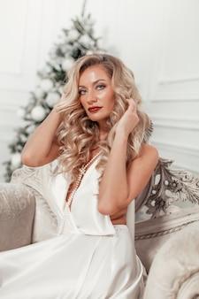 Портрет женщины в элегантном платье в помещении в длинном свадебном белом платье