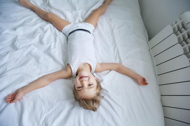 白い寝室に敷設幸せな子供。少年は自宅でパジャマを着てベッドで遊ぶ