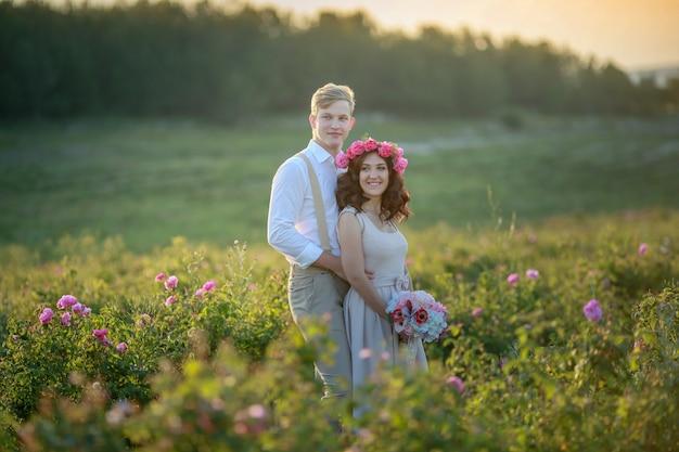 Счастливая молодая пара мужчина и женщина, взрослая романтическая семья. встречайте закат на пшеничном поле. счастливой улыбкой. девушка в руках держит подарок, букет цветов, из роз.