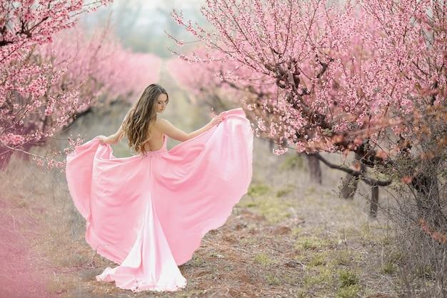 Жених в цветущем саду. женщина в длинном розовом платье.