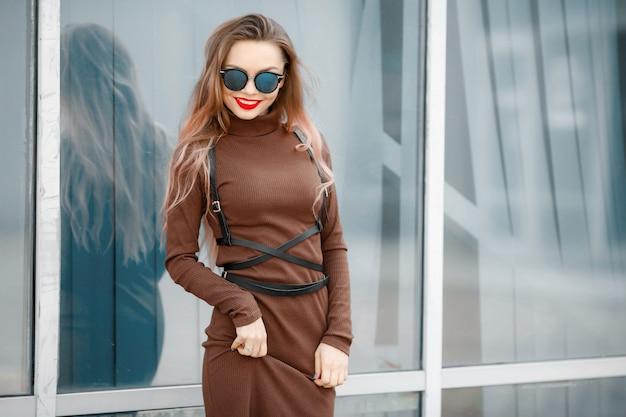 メガネと革のベルトが付いている通りのドレスを着た女性