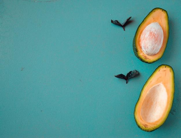 Половинки авокадо на деревянном фоне