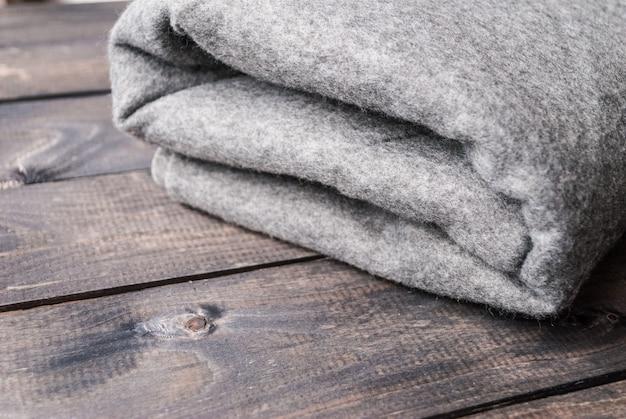 木製の背景に灰色の毛布