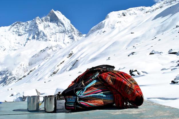 Рюкзак, шаль и кружки на столе со снежной вершиной