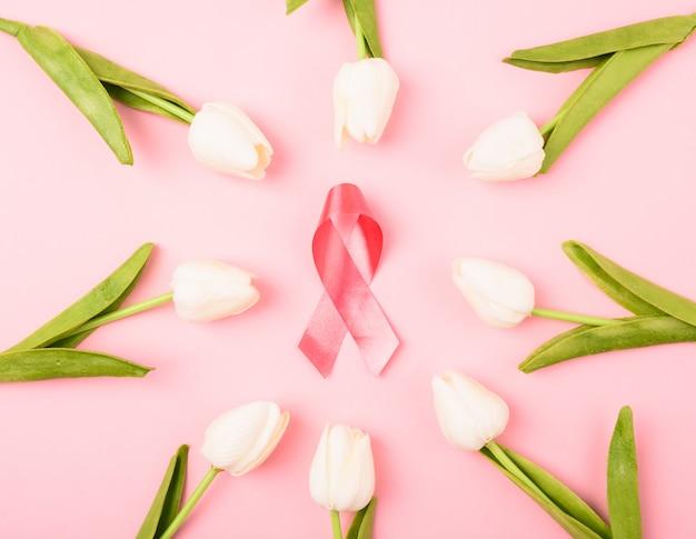 乳がん月、フラットレイアウトトップビュー、ピンクのリボンとチューリップの花