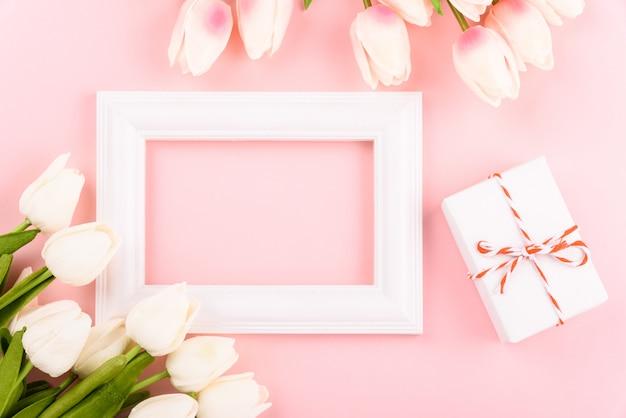 幸せな女性の日、母の日。ピンクのトップビューフラットレイアウトチューリップの花とフォトフレーム