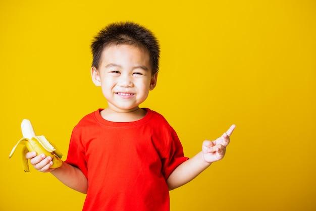 子供の小さな男の子は食べるために皮をむいたバナナの笑顔