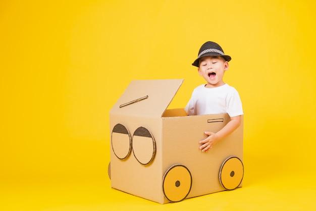 小さな子供男の子笑顔とても幸せなダンボール車を運転