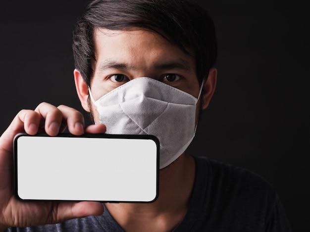 Человек, носящий защитную маску от страха показать мобильный телефон пустой экран