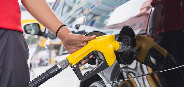 Персонал в униформе пользуется рукой, держащей пистолет для заправки автомобиля бензином