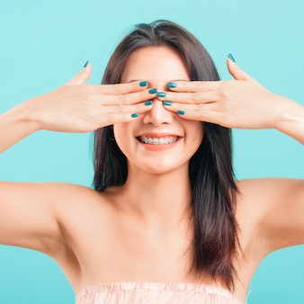 Улыбающееся лицо красивой азиатской женщины прикрывает глаза руками