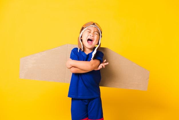 幸せなアジアの子小さな男の子の笑顔が立っている交差腕を飛んでいるおもちゃの段ボール飛行機の翼を持つパイロットの帽子を着用します。