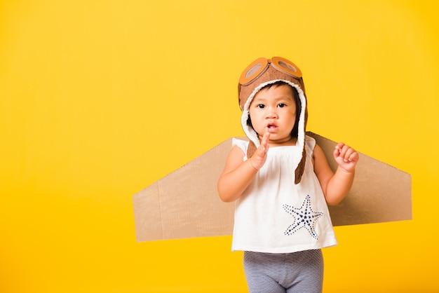 アジアの美しい赤ちゃん小さな女の子がおもちゃの段ボール飛行機の翼が飛んで遊んでパイロット帽子を着用します。