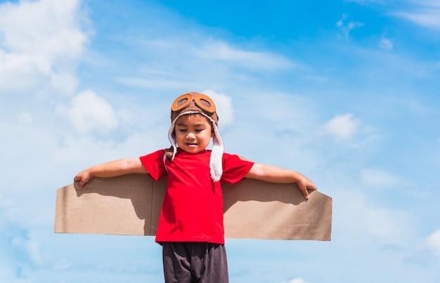 アジアの子小さな男の子の笑顔は、青い空に夏に対して屋外飛行おもちゃの段ボール飛行機の翼を持つパイロットの帽子を着用します。