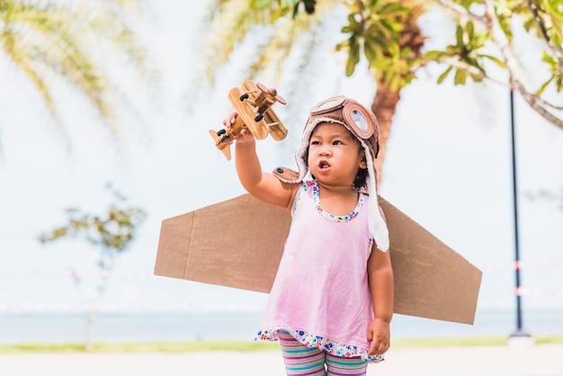 アジアの子供少女着用パイロット帽子遊びおもちゃ段ボール飛行機の翼が庭で夏の空を背景に飛んで
