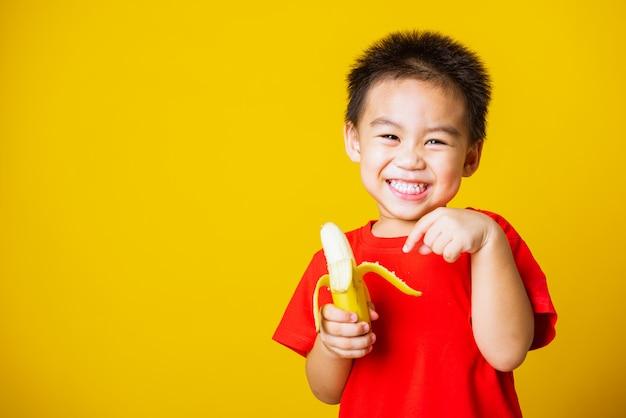 幸せなアジアの子少年の笑顔を保持している皮をむいたバナナ