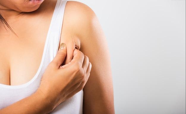 女性は彼女の脇の下を引っ張る彼女は脇の下の脂肪脇の下のしわのある皮膚に問題があります