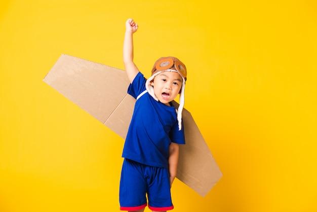 子供の小さな男の子の笑顔着用パイロット帽子遊びとおもちゃの段ボール飛行機の翼を持つゴーグル
