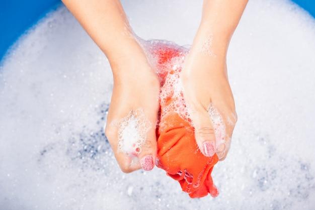 女性は流域で色の服を洗う手を使用します