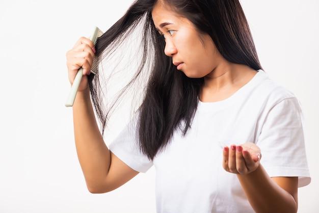 Женщина со слабыми волосами проблема ее использовать расческу расческу расчесывать ее волосы и показывая поврежденные длинные волосы выпадение щеткой на руке