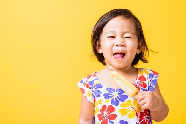 小さな女の子は甘いアイスキャンデーを保持します